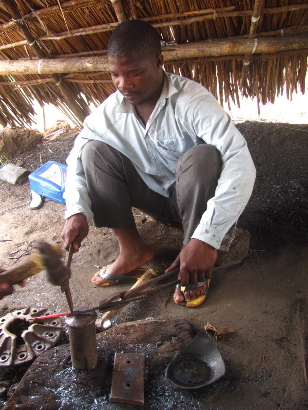Blacksmith at work, making big nails